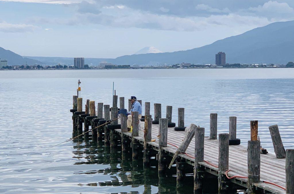 山の谷間から富士山が見える諏訪湖